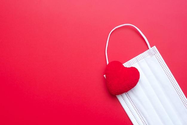 Décoration en forme de coeur et masque médical sur fond rouge contre l'infection par la maladie à coronavirus