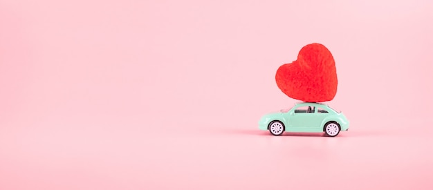 Décoration en forme de coeur rouge sur mini jouet de voiture avec espace de copie pour le texte sur rose. concept de vacances amour, mariage, romantique et bonne saint valentin
