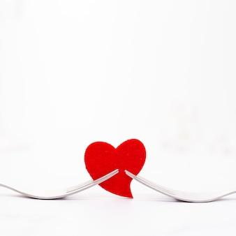 Décoration avec des fourches tenant un coeur rouge