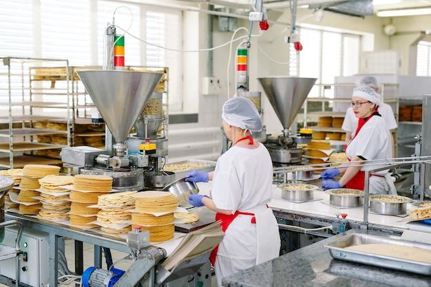 Décoration de gâteaux sur le convoyeur d'une usine de confiserie
