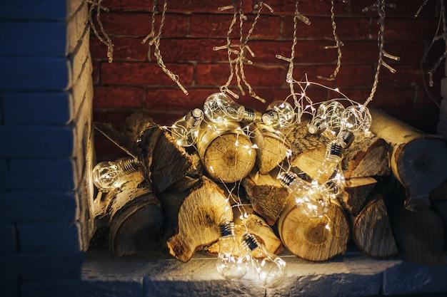 Décoration gerland ampoule de lumières de noël se trouvant dans la cheminée sur la conception de loft en bois de chauffage en bois