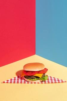 Décoration grand angle avec un cheeseburger savoureux sur une table jaune