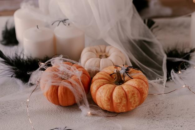 Décoration halloween effrayante avec différentes citrouilles, lumière, araignées.