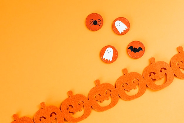 Décoration d'halloween avec une guirlande de citrouilles sur fond orange