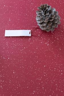 Décoration d'hiver pomme de pin avec étiquette sur fond rouge enneigé