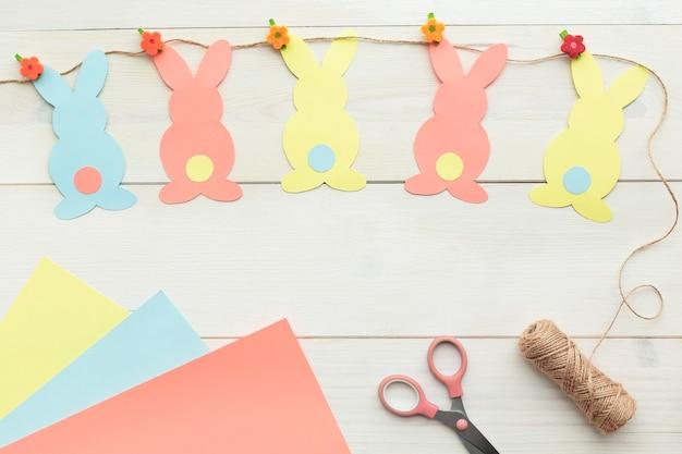 Décoration de lapin de pâques. papier découpé vacances bricolage lapins colorés et outils d'artisanat. vue de dessus, copiez l'espace sur fond en bois blanc.