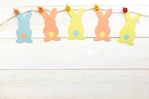 Décoration de lapin de pâques. papier découpé vacances bricolage lapins colorés.vue de dessus, copiez l'espace sur fond en bois blanc.