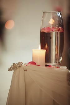 Décoration de mariage une bougie et un vase avec de l'eau sur une table blanche