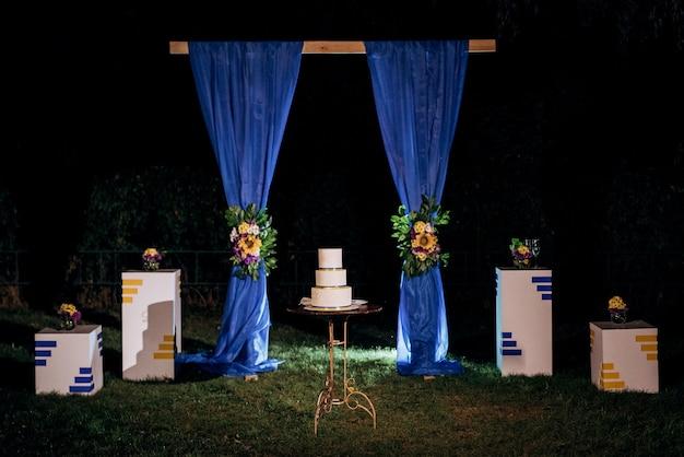 Décoration de mariage avec gâteau sur un banc en bois sur fond de cascade