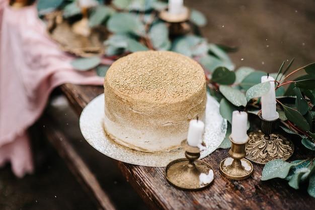 Décoration de mariage avec un gâteau doré sur un banc en bois sur fond de cascade
