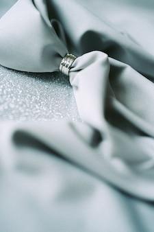 Décoration de mariage haute vue angle avec un tissu gris sur fond texturé gris. verticale