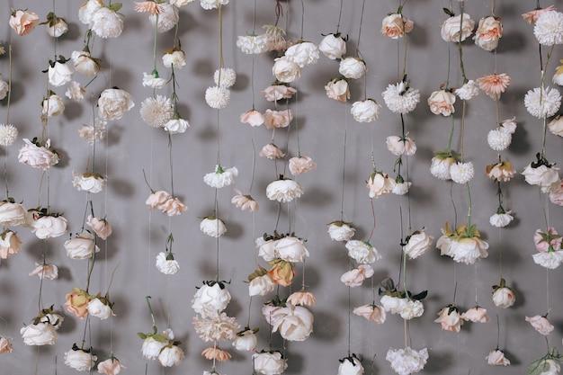 Décoration de mariage avec de nombreuses fleurs artificielles accrochées au mur gris.