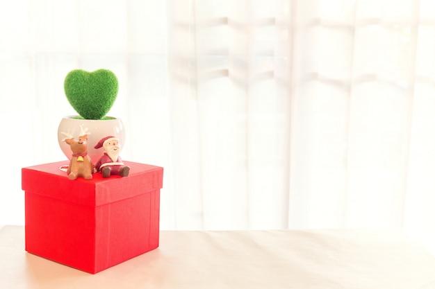 Décoration miniature de père noël et de renne avec une boîte d'emballage de colis rouge.