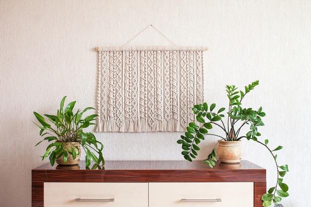 Décoration murale en macramé fait main 100 coton avec bâton en bois accroché sur un mur blanc tressage en macramé et fils de coton eco friendly concept de décoration naturelle à l'intérieur