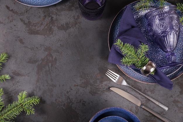 Décoration de noël bleu foncé avec une branche de sapin.
