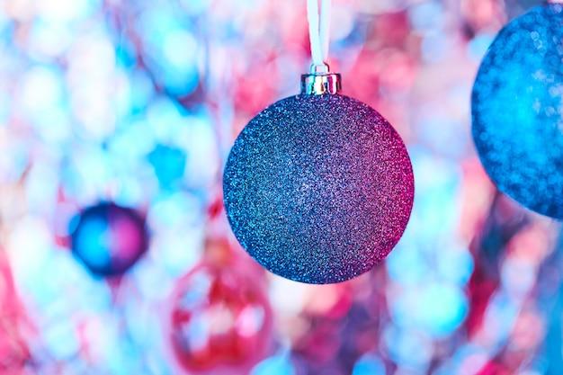 Décoration de noël bleue recouverte de minuscules paillettes argentées suspendues devant la caméra sur fond de noël coloré formé par d'autres boules de jouets