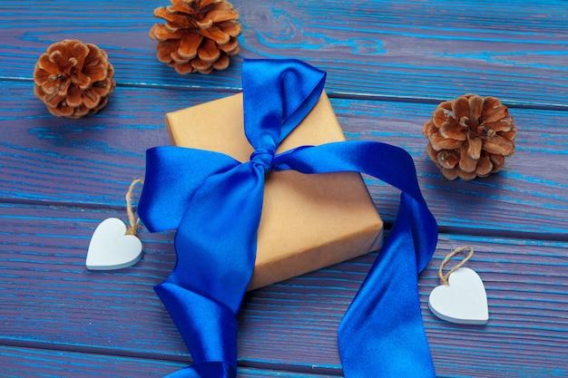 Décoration de noël, boîte de cadeau et branches d'arbres de pin sur fond en bois