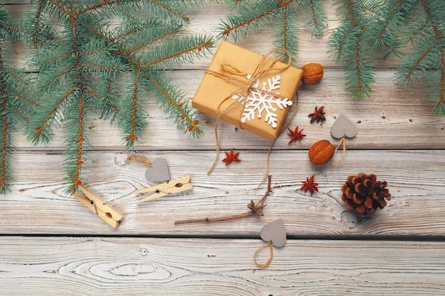 Décoration de noël, boîte-cadeau et branches d'arbres de pin sur une surface en bois