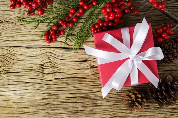 Décoration de noël de boîte-cadeau rouge et hiver rouge sur vieux bois