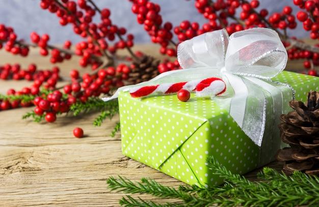 Décoration de noël de boîte de cadeau vert et hiver rouge sur vieux bois