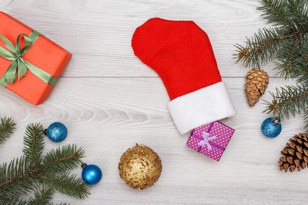 Décoration de noël. botte du père noël, coffret cadeau, branches de sapin avec cônes et jouets de noël sur planches grises. vue de dessus. concept de carte de voeux de noël.