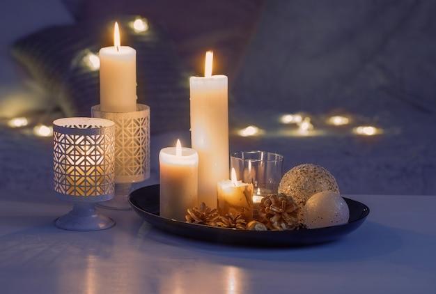 Décoration de noël avec des bougies allumées sur table blanche de canapé avec plaids et oreillers. concept de maison et de vacances confortable