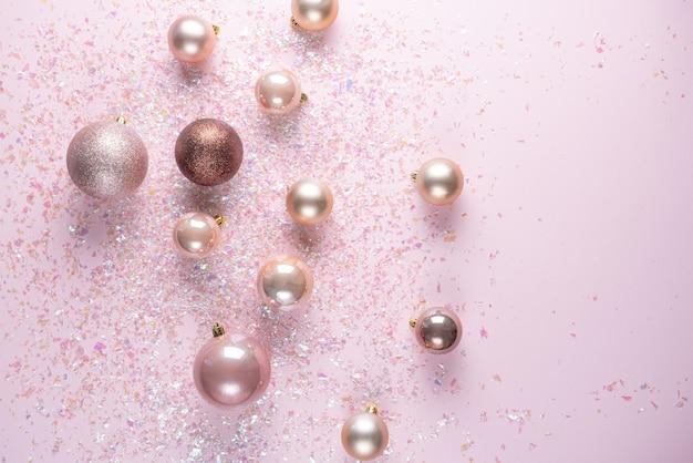 Décoration de noël de boules sur rose avec guirlandes. mise à plat avec copyspace