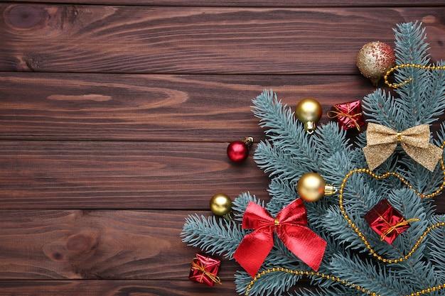 Décoration de noël. branche de sapin avec des boules, des cadeaux et des arcs sur un fond marron