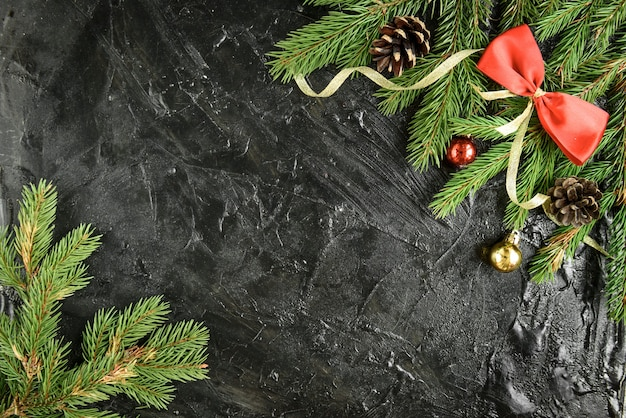 Décoration de noël. branche de sapin avec des boules, des cadeaux, une pomme de pin et des arcs sur une surface en bois noire