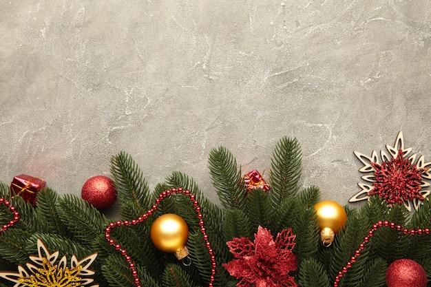 Décoration de noël. branche de sapin avec des boules rouges et or sur fond gris