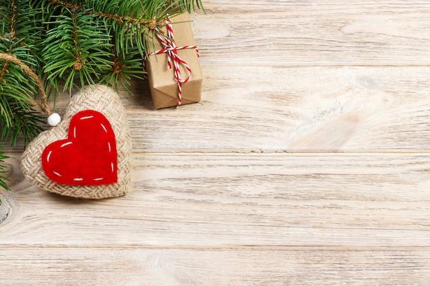 Décoration de noël avec des branches de sapin, un coeur tricoté et des coffrets cadeaux
