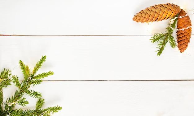 Décoration de noël branches de sapin vert, bosses et guirlande jaune sur planche de bois blanche.