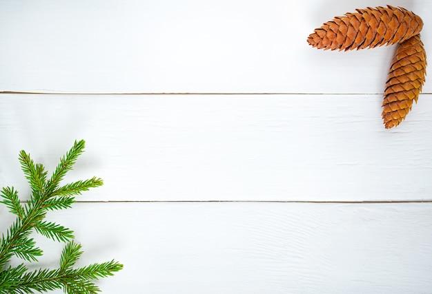 Décoration de noël branches de sapin vert et bosses sur planche de bois blanche.