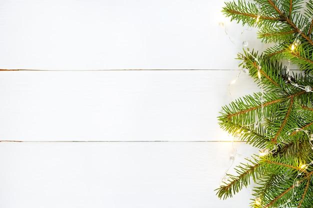 Décoration de noël branches de sapin vert et guirlande jaune sur planche de bois blanc.