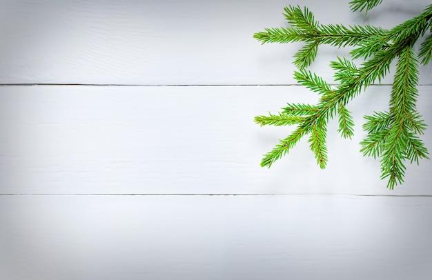 Décoration de noël branches de sapin vert sur planche de bois blanc.
