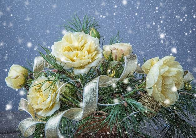 Décoration de noël. cadeau, bougies, lumières, boules dorées sur une table rustique en bois. composition de branches de pin et de roses anglaises dans un vase.