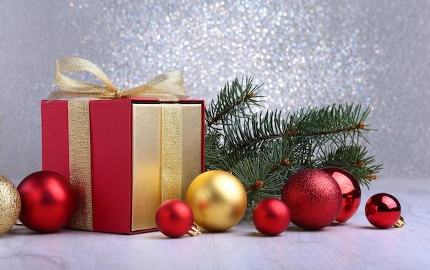 Décoration de noël avec des cadeaux et boule rouge avec des branches de sapin