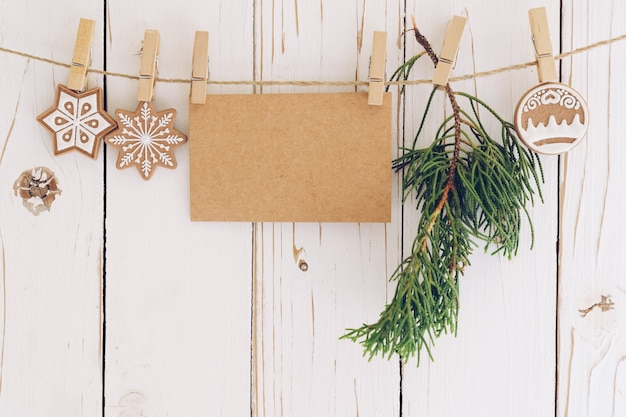Décoration de noël et carte de papier vierge accrochée sur fond de bois.