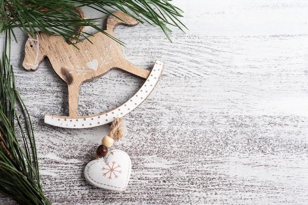 Décoration de noël avec cheval à bascule en bois et pin sur fond rustique blanc. copier l'espace