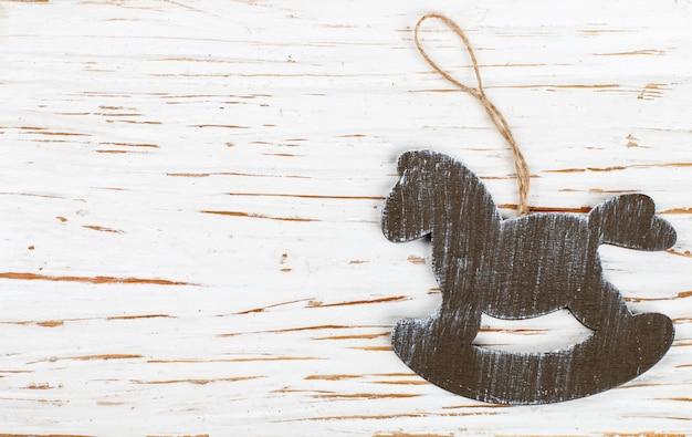 Décoration de noël, un cheval de bois sur une vieille table blanche. nouvel an.