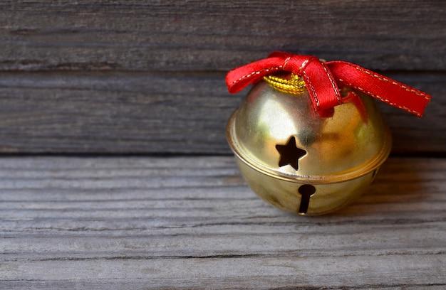 Décoration de noël avec cloche de noël dorée sur vieux bois. vacances d'hiver, concept de joyeux noël.