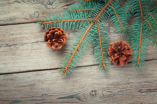 Décoration de noël avec des cônes de sapin et de pin sur un fond en bois blanc