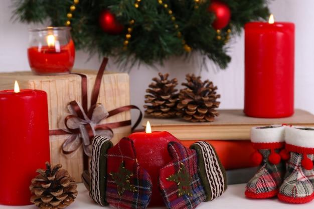 Décoration de noël avec couronne, bougies et coffrets cadeaux sur étagère sur une surface murale blanche