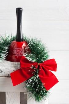 Décoration de noël dans un intérieur blanc scandinave avec arc rouge, cloche et bougie allumée. copiez l'espace pour le message d'accueil