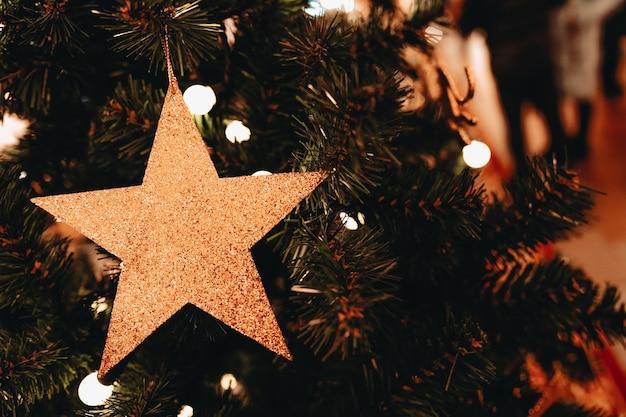 Décoration de noël dorée sur le sapin de noël jouet en forme d'étoile brillante joyeux noël