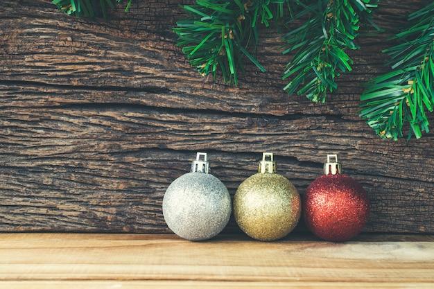 Décoration de noël sur fond en bois, boule de noël or, argent et rouge.