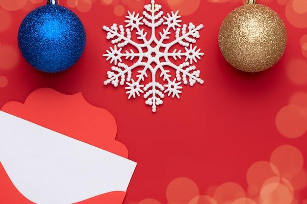 Décoration de noël sur fond rouge représentant deux boules de noël et un grand flocon de neige au centre