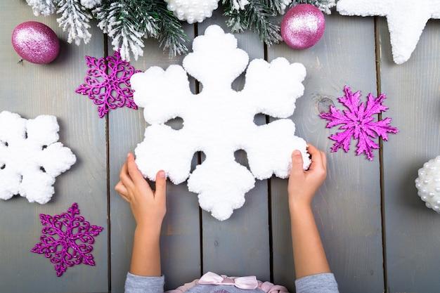 Décoration de noël. main d'enfant avec un snowlake décoratif. vue de dessus.