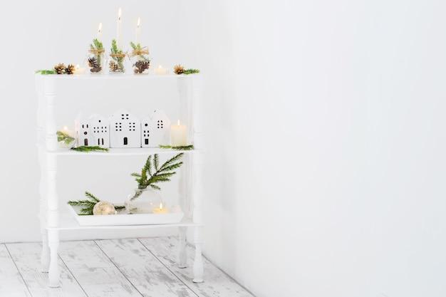 Décoration de noël à la maison avec des bougies allumées dans un intérieur blanc