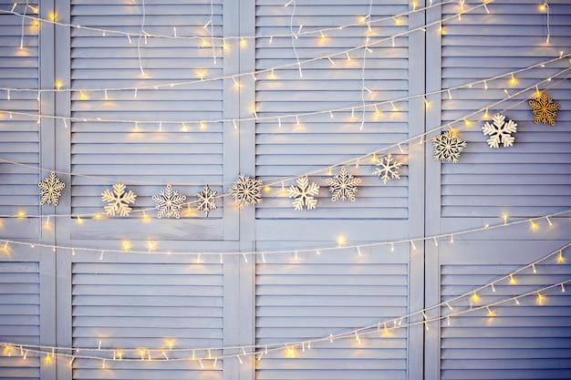 Décoration de noël sur le mur. guirlande de noël et lanternes en bois. texture ou arrière-plan. flocons de neige en bois